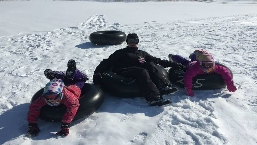 family of three on winter tubing hill in snow