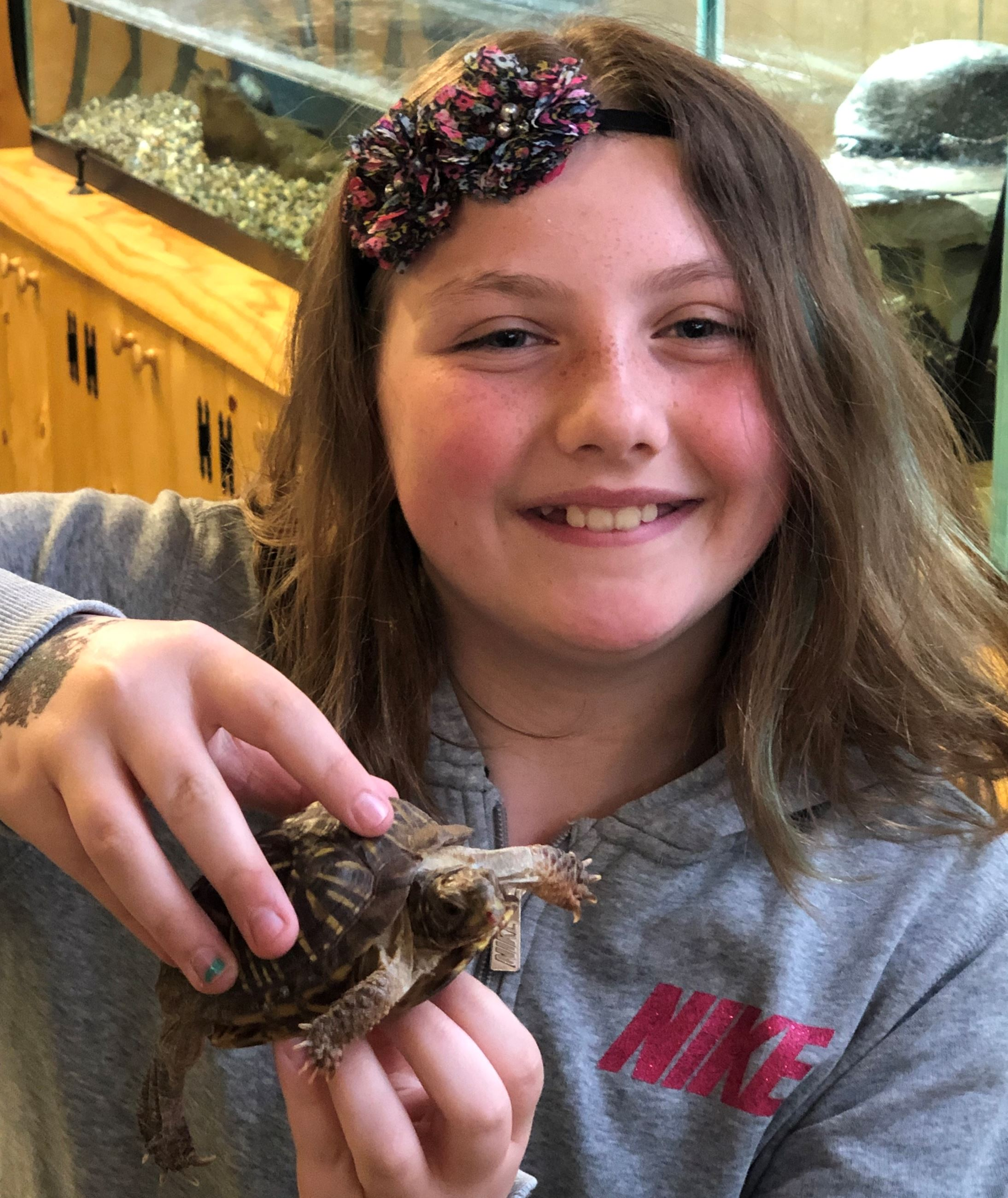 A girl holding a box turtle. She is smiling.